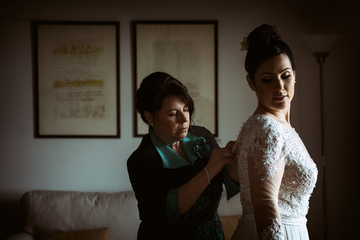 the mother helping the bride to wear her dress in a picture by Fabio Schiazza