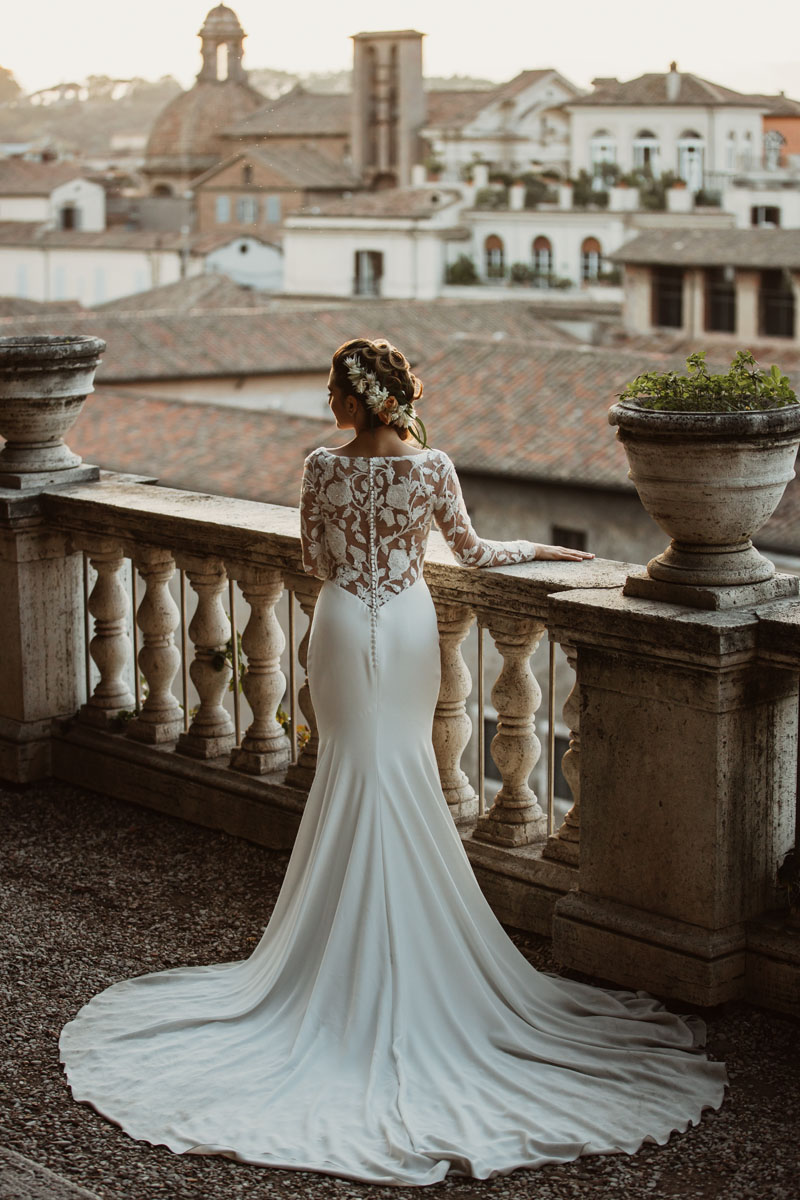 a beautiful bride with her white dress at sunset and a view of roman rooftops